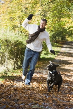 guy with walking stick: Man outdoors with dog on path in park holding branch smiling (selective focus)