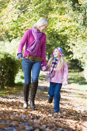 Woman and young girl walking outdoors in park and smiling photo