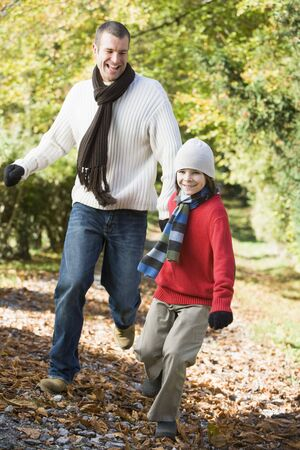 tweeny: Man and young boy running outdoors in park and smiling