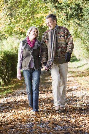 parejas caminando: Pareja al aire libre para caminar en la ruta en el parque de la mano y sonriendo (enfoque selectivo)
