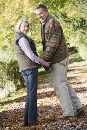 ancianos caminando: Mayor al aire libre en la ruta en el parque tomados de la mano y sonriendo (atenci�n selectiva)