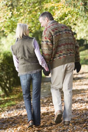 woman behind: Couple outdoors walking on path in park holding hands and smiling (selective focus)