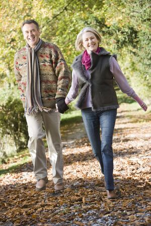 retirement: Couple outdoors running on path in park holding hands and smiling (selective focus) Stock Photo