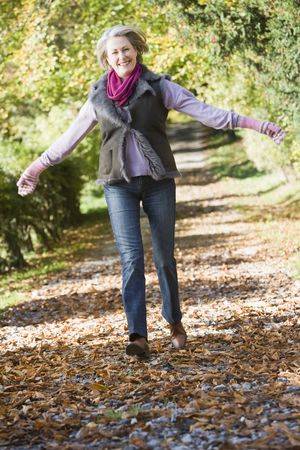 caucasoid race: Woman outdoors at park running on path and smiling (selective focus) Stock Photo