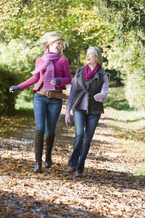 Two women running outdoors in park and smiling photo