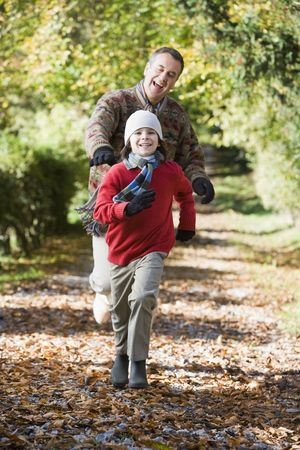 tweeny: Grandfather and grandson running outdoors in park and smiling Stock Photo