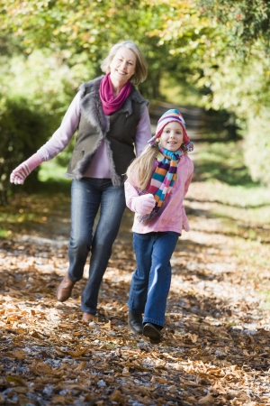 Grandmother and granddaughter running outdoors in park and smiling photo