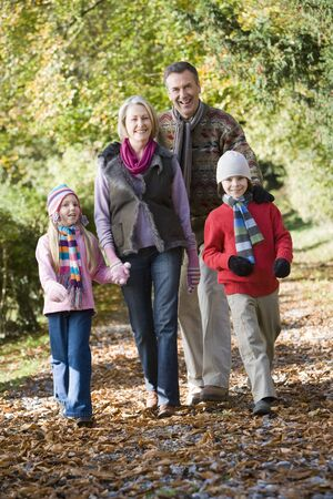Grandparents walking with grandchildren outdoors in park and smiling photo