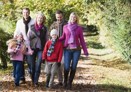 adult offspring: Family walking outdoors in park and smiling Stock Photo