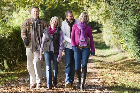 couple holding hands: Two couples walking outdoors in park and smiling Stock Photo