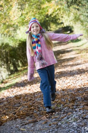 caucasoid race: Young girl outdoors at park running on path smiling (selective focus) Stock Photo