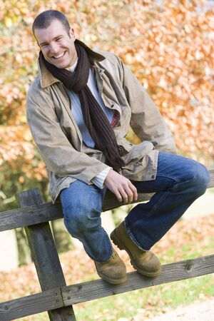 Man outdoors at park sitting on fence smiling (selective focus) Stock Photo - 3217782
