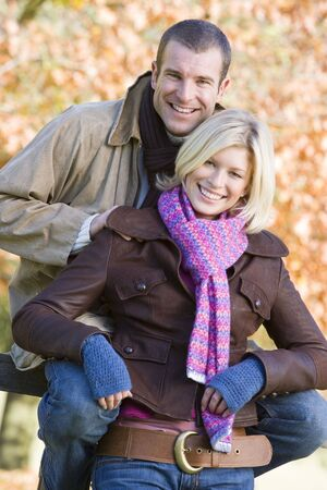 caucasoid race: Couple outdoors in park by fence smiling (selective focus) Stock Photo
