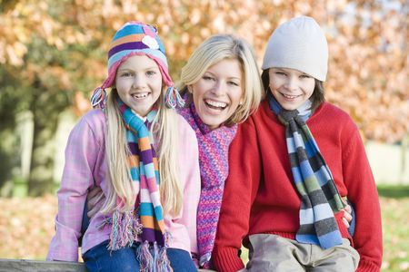 tweeny: Mother and two young children outdoors in park smiling Stock Photo