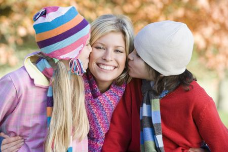 Mother and two young children outdoors in park smiling photo