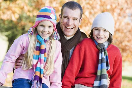 tweeny: Father and two young children outdoors in park smiling (selective focus)