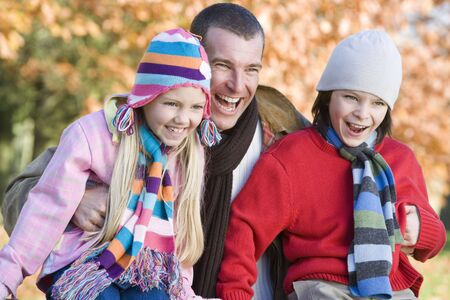 tweeny: Father and two young children outdoors in park laughing (selective focus) Stock Photo