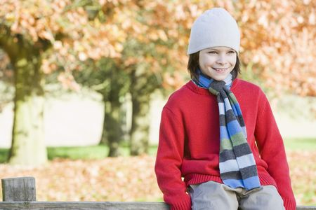 tweeny: Young boy outdoors at park sitting on fence smiling (selective focus)