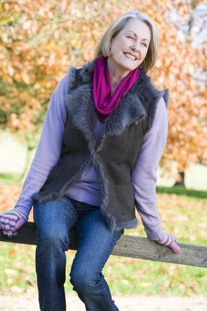 offset angle: Woman outdoors at park sitting on fence smiling (selective focus)