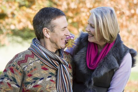 caucasoid race: Couple outdoors in park bonding and smiling (selective focus)