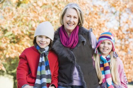Grandmother and two children outdoors in park smiling (selective focus) photo