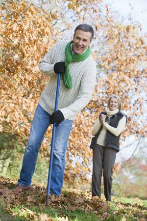 Man outdoors raking leaves and woman in background smiling (selective focus) photo