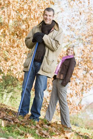 Man outdoors raking leaves and woman in background smiling (selective focus) Stock Photo - 3217811