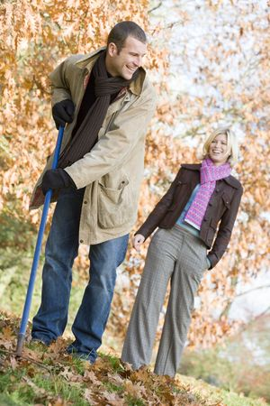 offset angles: Man outdoors raking leaves and woman in background smiling (selective focus) Stock Photo