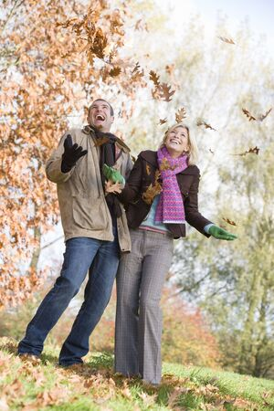 Couple outdoors playing in leaves and smiling (selective focus) photo