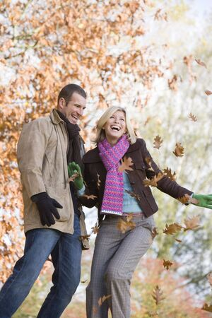Couple outdoors playing in leaves and smiling (selective focus) Stock Photo - 3226333