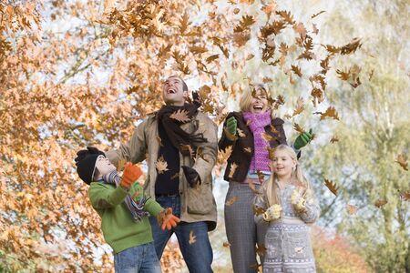 hermanos jugando: Familia en el parque al aire libre jugando en las hojas y sonriente (atenci�n selectiva)  Foto de archivo