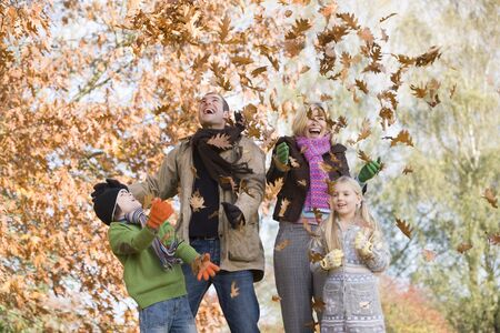 adult offspring: Family outdoors in park playing in leaves and smiling (selective focus)