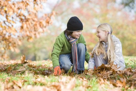 Two young children outdoors in park playing in leaves and smiling (selective focus) photo