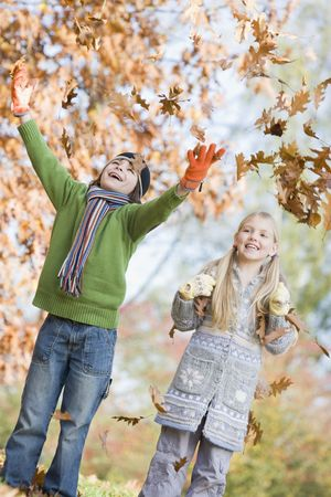 caucasoid race: Two young children outdoors in park playing in leaves and smiling (selective focus) Stock Photo