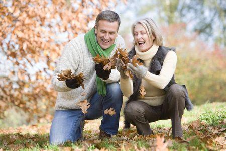 Paar buitenshuis kijken bladeren en lachend (selectieve aandacht)
