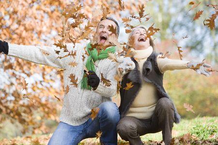 야외에서 나뭇잎에 재생 및 (선택적 포커스) 웃는 몇 야외에서 나뭇잎에 재생 및