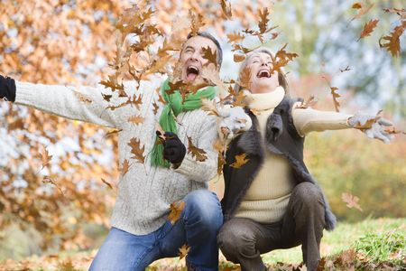 Couple outdoors playing in leaves and smiling (selective focus) Stock Photo