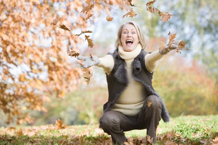 Woman outdoors throwing leaves up and smiling (selective focus) Stock Photo - 3226344