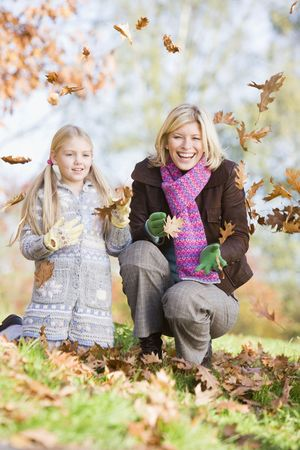fall fun: Woman and young girl outdoors in park playing in leaves and smiling (selective focus) Stock Photo