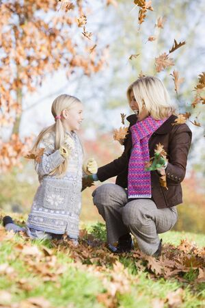 caucasoid race: Woman and young girl outdoors in park playing in leaves and smiling (selective focus) Stock Photo