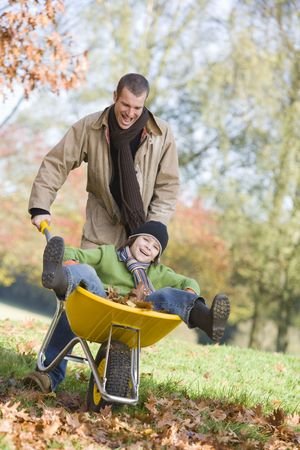 offset angles: Man and young boy outdoors playing with wheelbarrow and smiling (selective focus)