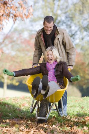30s adult: Man outdoors pushing woman in wheelbarrow and smiling (selective focus)