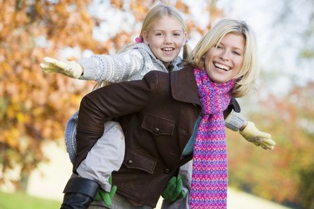 Mother outdoors piggybacking daughter and smiling (selective focus) Stock Photo - 3226345
