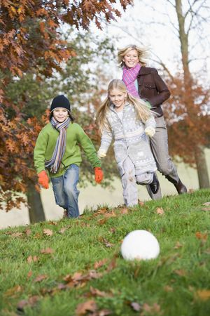 Mother outdoors in park with two young children playing soccer and smiling (selective focus) photo