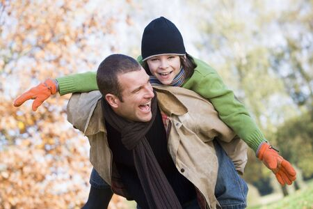 caucasoid race: Father outdoors piggybacking son and smiling (selective focus) Stock Photo