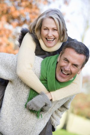Senior man outdoors piggybacking woman and smiling (selective focus) photo