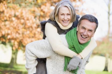 Senior man outdoors piggybacking woman and smiling (selective focus)  Stock Photo - 3226324