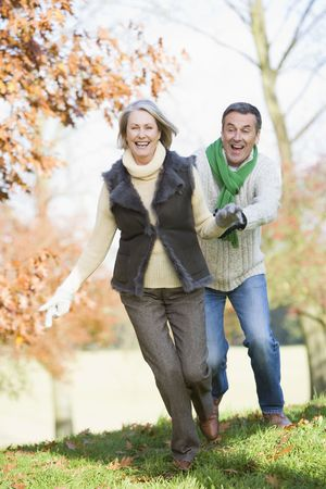 Senior couple outdoors running around and smiling (selective focus) photo