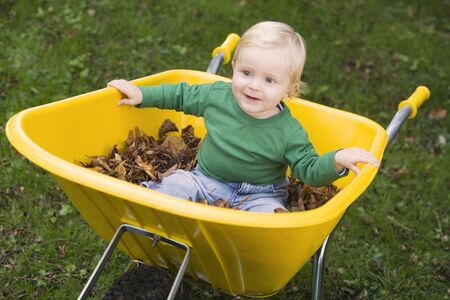 outdoors sitting in wheelbarrow smiling (selective focus) Stock Photo - 3218032