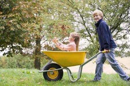 caucasoid race: Young boy outdoors pushing young girl in wheelbarrow and smiling (selective focus)
